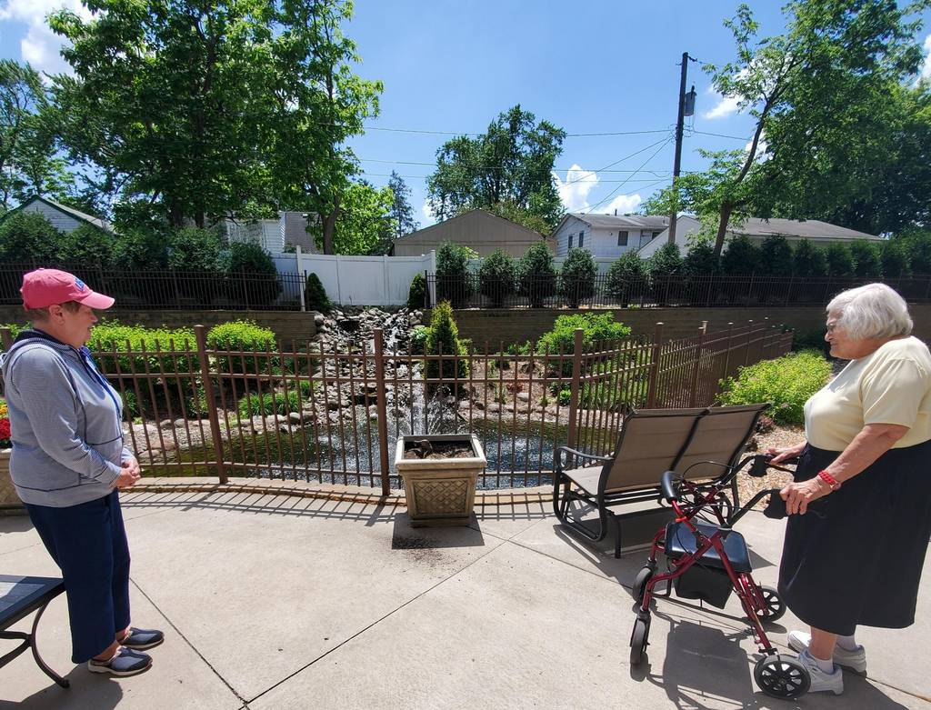 An image of two residents enjoying time outside at The Legacy of St. Anthony, St. Anthony.